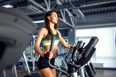 Young fitness woman doing cardio exercises at the gym running on a treadmill. Female runner training at the health club Royalty Free Stock Photography