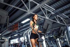 Young fitness woman doing cardio exercises at the gym running on a treadmill. Female runner training at the health club Stock Images