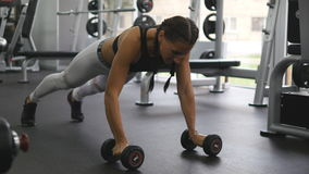 Young fitness woman doing dumbbell rows at crossfit gym. Sportive girl exercising - pulls weight. Beautiful female Stock Photos