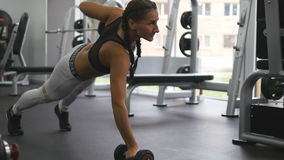 Young fitness woman doing dumbbell rows at crossfit gym. Sportive girl exercising - pulls weight. Beautiful female Royalty Free Stock Photography
