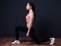 Young fitness woman doing exercise. Young fitness woman doing lunge with squats royalty free stock photography