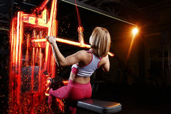 Young fitness woman doing exercises the major muscle groups in the gym. Strength training. Fiery training machine. Stock Images