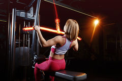 Young fitness woman doing exercises the major muscle groups in the gym. Strength training. Fiery training machine. Stock Photos