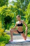 Young fitness woman doing fitness exercises in the park on green. Grass. Fitness training outdoors. Fitness classes outdoors. Attractive fitness woman. Workout Stock Photo