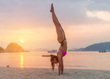Young fitness woman doing handstand exercise on beach at sunrise. Sporty girl in bikini practicing yoga seashore. Young fitness woman doing handstand exercise Stock Image