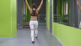 Young fitness woman doing lunge with barbell and flexing muscles in gym. Girl training - attacks with a barbell at stock footage
