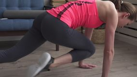 Young fitness woman doing mountain climber workout on floor at home stock footage