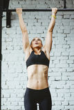 Young fitness woman doing pull ups in gym Stock Photos