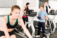 Young fitness woman doing spinning with instructor. Young fitness woman doing spinning on bicycle with gym instructor Stock Image