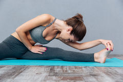 Young fitness woman doing splits isolated on grey background Stock Photography