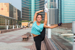 Young fitness woman doing standing split exercise on the city street. Sporty fit girl working out outdoors stretching Stock Photos