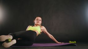 Young fitness woman doing training with dumbbells in legs - attractive fitness model in studio. Close up stock footage