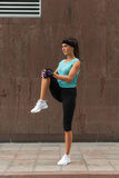 Young fitness woman doing warm-up exercise before running stretching her leg by performing knee to chest stretch on the Stock Images