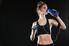 Young Fitness woman drinking water. In studio over black background Stock Image