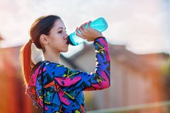 Fitness woman drinking water after training stock image