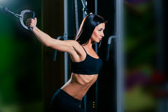 Young fitness woman execute exercise with exercise-machine Cable Crossover in gym, horizontal photo Royalty Free Stock Images