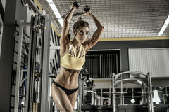 Young fitness woman execute exercise with exercise-machine Cable Stock Photography