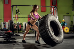 Young fitness woman execute exercise with tire casing, in gym Stock Photography