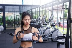 Young fitness woman exercise workout with exercise-machine Cable in fitness center gym. healthy lifestyle Concept. Young fitness woman exercise workout with stock images