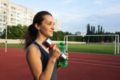 Young fitness woman holding the dumbbell and a water bottle at the stadium. Empty space stock image