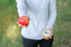 Young fitness woman holding in hands red apple and donut royalty free stock photography
