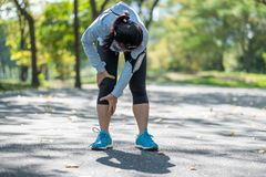 Young fitness woman holding his sports leg injury, muscle painful during training. Asian runner having calf ache and problem after. Running and exercise outside stock photos