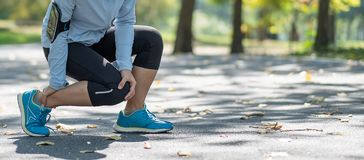 Young fitness woman holding his sports leg injury, muscle painful during training. Asian runner having calf ache and problem after. Running and exercise outside stock image
