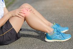 fitness woman holding his sports leg injury, muscle painful during training royalty free stock images