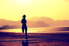 Young fitness woman jogging at beach Royalty Free Stock Image