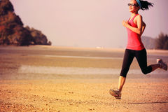 Young fitness woman jogging at beach Stock Images
