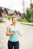 Young fitness woman jogging on cobbled road. Young happy fitness woman jogging on cobbled street of hillside town Stock Photography