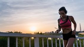 Young fitness woman jogging outdoors in the city over bridge. In the sunset Stock Photography