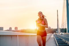 Young fitness woman jogging outdoors in the city over bridge. In the sunset Royalty Free Stock Images