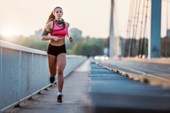 Young fitness woman jogging outdoors in the city over bridge. In the sunset Stock Photos