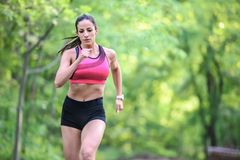 Young fitness woman jogging in the park. Young fitness woman jogging in in the park. Fast woman running Stock Photos