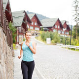 Young fitness woman jogging on street of town. Young smiling fitness woman jogging on cobbled street of hillside town Royalty Free Stock Photo