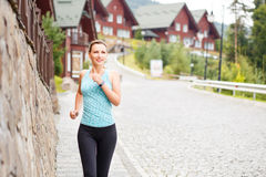 Young fitness woman jogging on street of town. Young smiling fitness woman jogging on cobbled street of hillside town Stock Photos