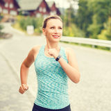 Young fitness woman jogging on street of town. Young smiling fitness woman jogging on cobbled street of hillside town. Warm color toned image Stock Photography