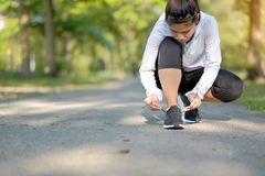 Young fitness woman legs walking in the park outdoor, female runner running on the road outside, asian athlete jogging and exercis. E on footpath in sunlight royalty free stock image