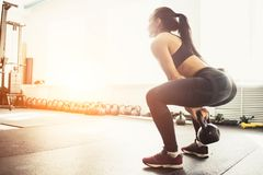 Young fitness woman lifting heavy weight kettle bell at gym. Athletic woman exercising with kettle bell while being in squat position. Muscular woman doing royalty free stock images