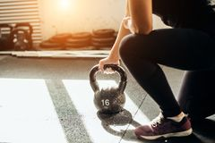 Woman standing on knee and preparing for cross fit exercise. Young fitness woman lifting a heavy weight kettle bell at gym. Caucasian female athlete working out Royalty Free Stock Images