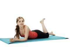 Young fitness woman lying on a blue mat Stock Photos