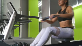 Young fitness woman make exercise on rowing machine in gym. Female athlete training at exerciser in health club. Girl. With perfect fitness body in sportswear stock footage