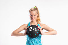 Young fitness woman with medicine ball. Studio shot. Royalty Free Stock Images