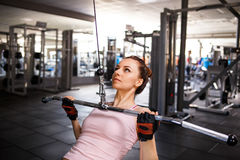 Young fitness woman performing lats pulldown Royalty Free Stock Photography