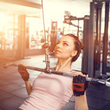 Young fitness woman performing lats pulldown Royalty Free Stock Image