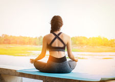 Young fitness woman practicing yoga on the field, healthy lifestyle concept. royalty free stock photos
