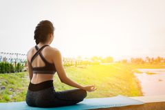Young fitness woman practicing yoga on the field, healthy lifestyle concept. royalty free stock photography