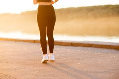 Young fitness woman runner legs running on seaside mountain trail stock photo