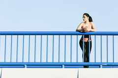 Young fitness woman runner running on city bridge. Royalty Free Stock Images